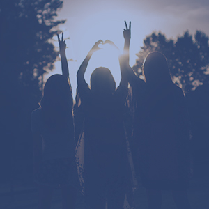 3 women in silhouette, making peace and heart signs with their fingers
